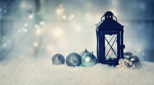 Christmas lantern with ornaments in the snow at night