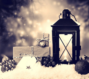Christmas lantern with presents, ornaments and snow in sepia tone