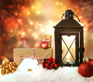 Christmas lantern with presents, ornaments and snow on a orange shinning night background