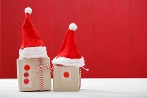 Christmas little gift boxes with Santa hats on red colored wooden board