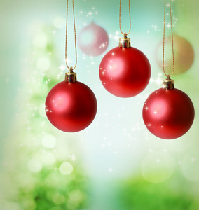 Christmas red ornaments over green tree lights background