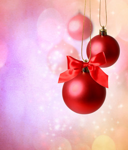 Christmas red ornaments over pink  lights background