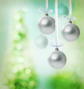 Christmas snowflake ornaments over green tree lights background