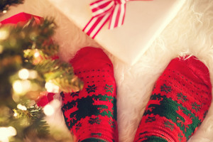 Christmas socks and gift box on a white carpet at night