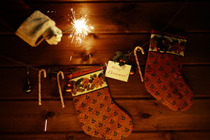 Christmas socks, sugar canes, toy bubbles on wooden background and Bengal light in gloved Santa hand