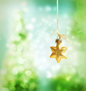 Christmas star ornament over green tree lights background