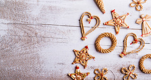 Christmas straw decoration. Studio shot on white wooden background.