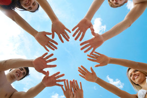 Circle of people' hands on blue sky background