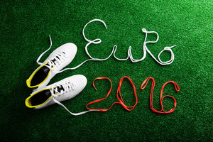 Cleats and Euro 2016 sign made of shoelaces against artificial turf, studio shot on green background. Flat lay.