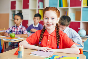 Clever schoolgirl looking at camera while sitting by desk