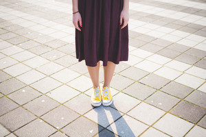 clolse up of modern young woman legs with skirt and yellow shoes