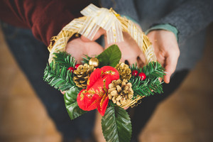 Close uo on the hands of man and woman couple holding and showing a crown decoration - christmas, decoration, celebration concept