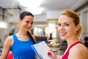 Close up, attractive fit woman in a gym consulting  work out with personal trainer, exercise plan on clipboard