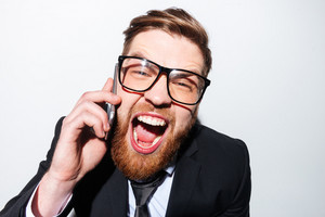 Close up Business man in glasses and suit screaming in phone with open mouth. Isolated gray background