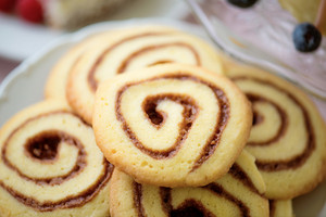 Close up cookies in shape of spiral laid on white plate. Studio shot.