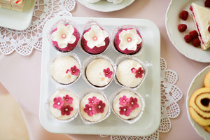 Close up, cupcakes on tray decorated with white and pink flowers laid on table with pink tablecloth and handmade lace. Candy bar.