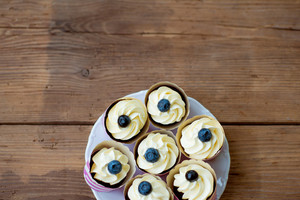 Close up, cupcakes with vanilla cream decorated with blueberries, laid on white plate. Copy space. Studio shot on brown wooden background. Flat lay.