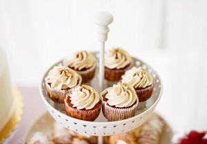 Close up, cupcakes with vanilla cream in white cakestand. Studio shot.