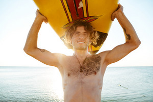 Close up face of handsome smiling curly guy with surfboard on head at beach