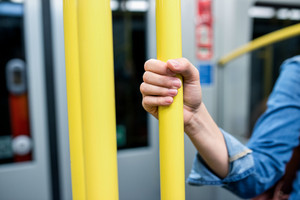 Close up, hand of unrecognizable woman in denim shirt traveling by subway train, holding yellow handrail tightly