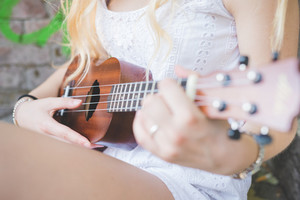 Close up hand young millennial caucasian woman playing ukulele - music, song, chord concept