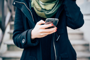 close up hands of young beautiful hipster woman in town using smartphone