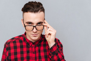 Close up Handsome hipster in red shirt looking at camera and holding his glasses. Isolated gray background
