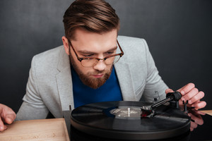 Close up hipster with gramophone in studio. sitting on table. isolated black background
