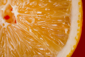 Close up image of aa fresh slice of orange isolated on red background