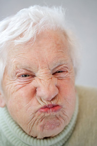 Close up image of senior woman grimacing