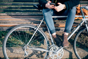 close up legs and hands young hipster sporty blonde woman in town with bike using smartphone