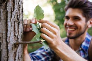 Close up man near the tree. focus on tree. smiling man
