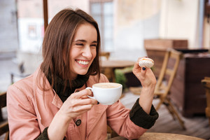 Close up model in coat at cafe. smiling. with macarons and cup of coffee