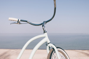 Close-up of a blue retro bicycle against the sea on the beach. Biking on a summer evening.