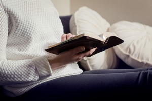 Close-up of a christian woman reading the bible. Sitting in sofa.