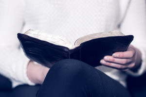 Close-up of a christian woman reading the holy bible. Sitting in sofa.