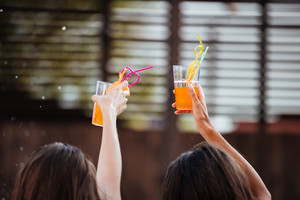 Close up of a female hands holding alcohol drinks outdoors