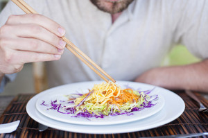 Close up of a man enjoying a meal with chopsticks in vietnamese restaurant