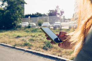 Close-up of a mobile phone in a female hand on the background of the city in the sunlight. Woman walks down the street and looking at the phone's screen.