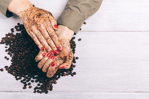 Close-up of a woman applying coffee scrub to her hands, top view