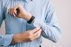 Close-up of a woman buttoning a shirt. The girl is going to work.
