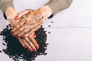 Close-up of a woman puts on hands with red manicure a coffee scrub, top view