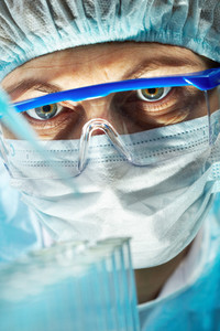 Close-up of a woman wearing protective mask and eyeglasses working with bio samples