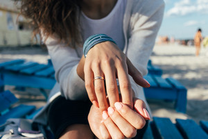 Close up of a Woman with a ring on her finger sitting on a bench on the beach