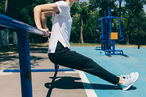 Close-up of a young athletic woman doing exercises for the triceps on the playground in the summer. Concept of a healthy lifestyle.