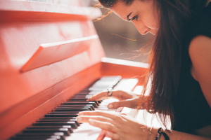 Close up of a young beautiful reddish brown hair caucasian girl playing piano - creative, performance, music concept - she is dressed with a black shirt and plays a red piano