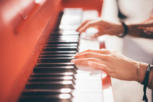Close up of a young beautiful reddish brown hair caucasian girl plyaing piano - creative, performance, music concept - she is dressed with a black shirt and plays a red piano