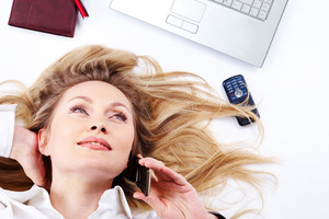 Close-up of a young businesswoman lying and chattering on the phone