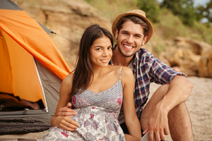 Close up of a young happy beautiful couple sitting at the tent at the beach