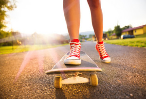 Close up of a young skater girl's feet and skateboard